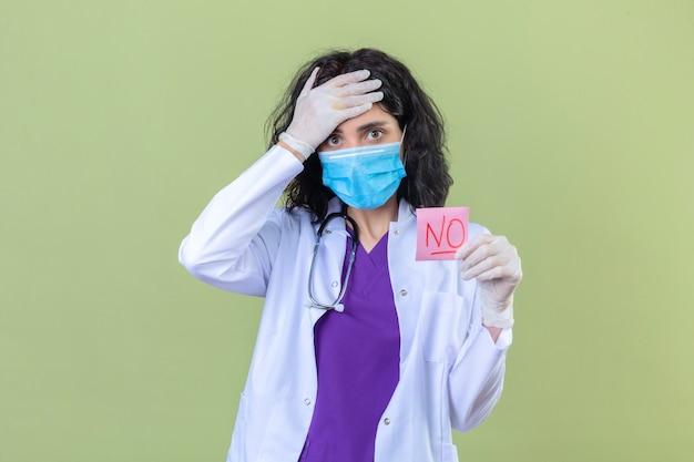Femme médecin portant une blouse blanche avec stéthoscope dans un masque de protection médicale tenant un papier de rappel sans mot à la surprise de toucher la tête avec la main sur vert isolé