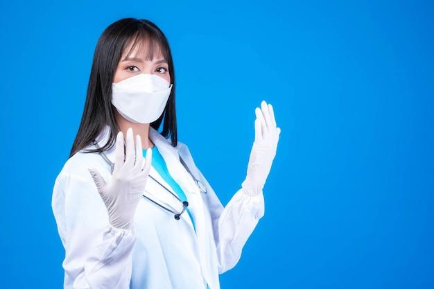 Femme médecin portant une blouse médicale blanche, des gants de masque facial stériles et des gants en caoutchouc avec stéthoscope isolés sur fond bleu, espace de copie - protéger la propagation du concept coronavirus covid-19