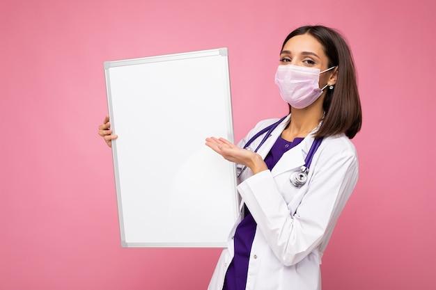 Femme médecin portant une blouse médicale blanche et un masque tenant un tableau blanc avec espace de copie pour le texte isolé sur fond. notion de coronavirus.