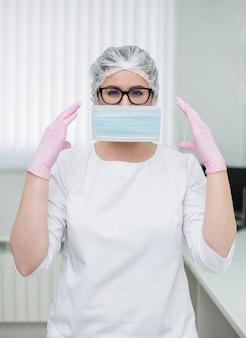 Femme médecin portant des lunettes dans un costume médical blanc, une casquette et des gants jetables met un masque médical