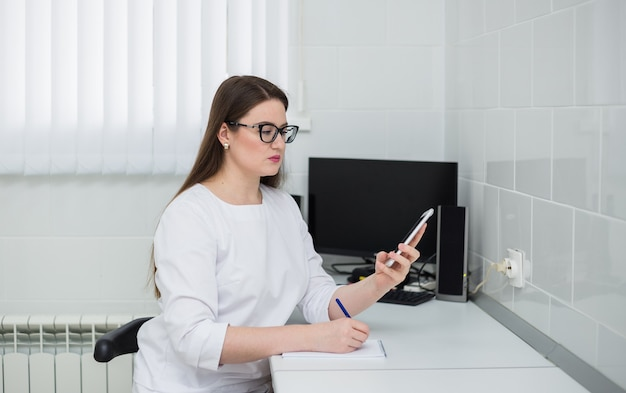 Une femme médecin portant des lunettes et un uniforme médical blanc est assise à un bureau et prend des notes au téléphone