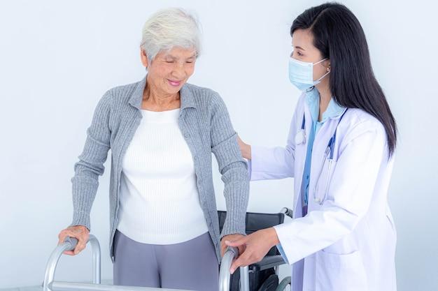 Femme médecin portant un masque médical soutenant une femme âgée en utilisant une marchette. soins aux patients âgés et soins de santé, concept médical.