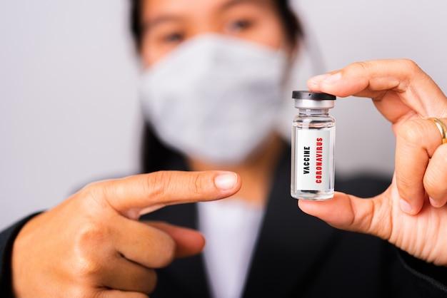 Femme médecin portant un masque protecteur contre le coronavirus son vaccin bouteille ampoule de pointage