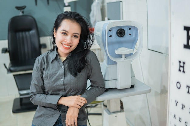 Une femme médecin posant à côté d'un kit de test oculaire situé dans une salle d'examen à la clinique ophtalmologique