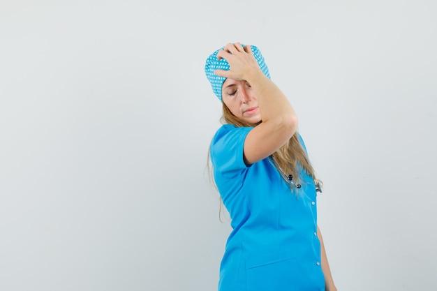 Femme médecin posant avec la main sur la tête en uniforme bleu