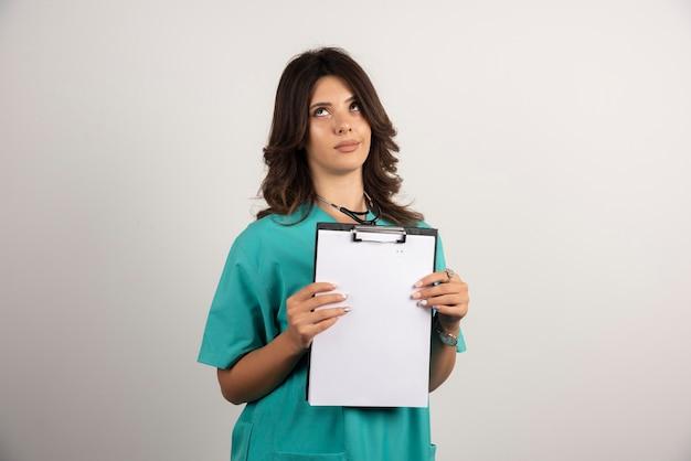 Femme médecin posant avec presse-papiers sur blanc