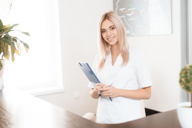 Une femme médecin pose à la réception de l'hôpital.