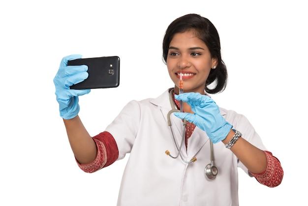 Femme médecin prenant selfie avec stéthoscope et injection par smartphone sur fond blanc.