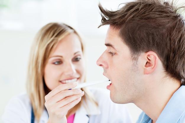 Femme médecin prenant la température de son patient