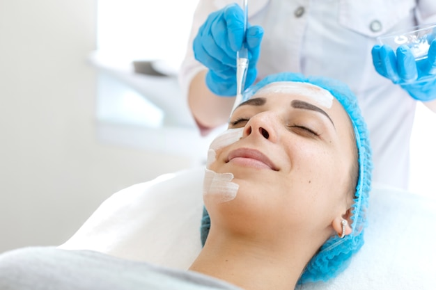 Femme médecin professionnel esthéticienne applique un masque sur le visage d'un patient pour les soins de la peau