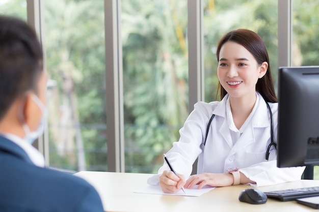 Une femme médecin professionnelle asiatique qui porte un manteau médical s'entretient avec un patient à consulter