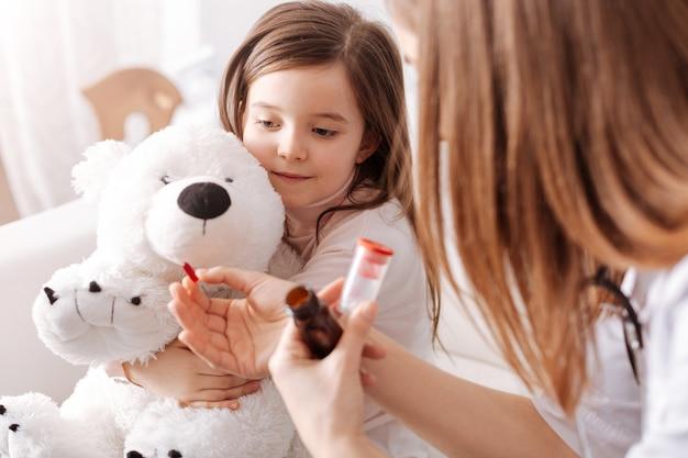 Femme médecin professionnelle tenant des pilules et donnant à une petite fille pendant qu'elle tient son jouet moelleux