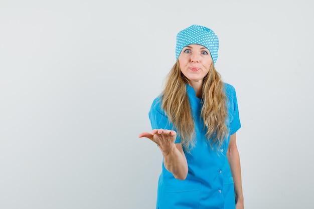 Femme médecin qui s'étend de la main dans le geste d'interrogation en uniforme bleu