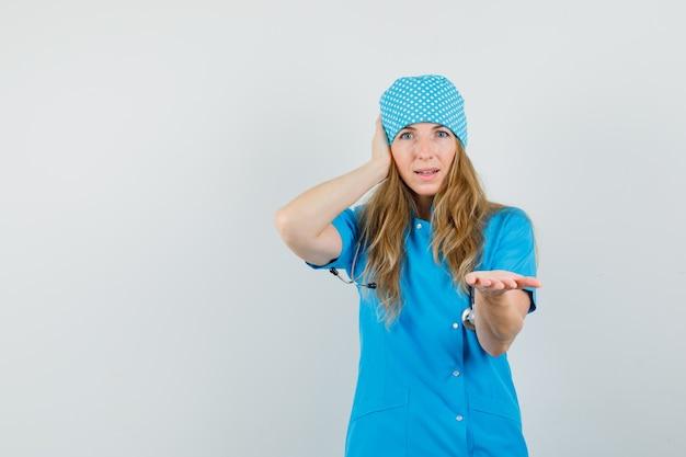 Femme médecin qui s'étend de la paume et tenant la main sur l'oreille en uniforme bleu