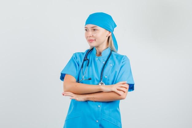 Femme médecin à la recherche de côté avec les bras croisés en uniforme bleu et à la recherche d'espoir.
