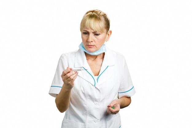 Femme médecin à la recherche sur le thermomètre. infirmière d'âge moyen fronçant les sourcils vérifiant la température, blanc.