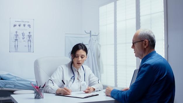 Femme médecin recommandant des pilules dans son bureau à un homme âgé à la retraite. bilan de santé d'un hôpital ou d'une clinique privée moderne pour la prévention des maladies et les problèmes de santé. plaintes des patients et
