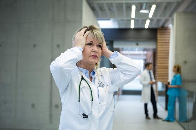 Femme médecin réfléchie debout n couloir