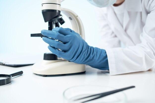 Femme médecin regardant à travers un laboratoire de recherche en biotechnologie au microscope