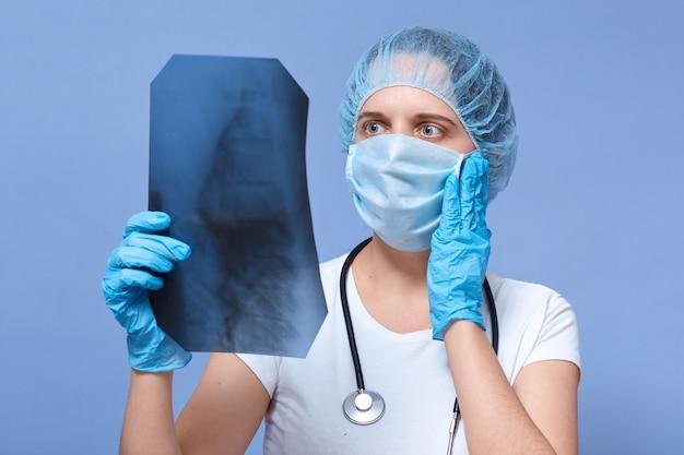 Femme médecin regardant x rayons des poumons, ayant une expression faciale étonnée et effrayée