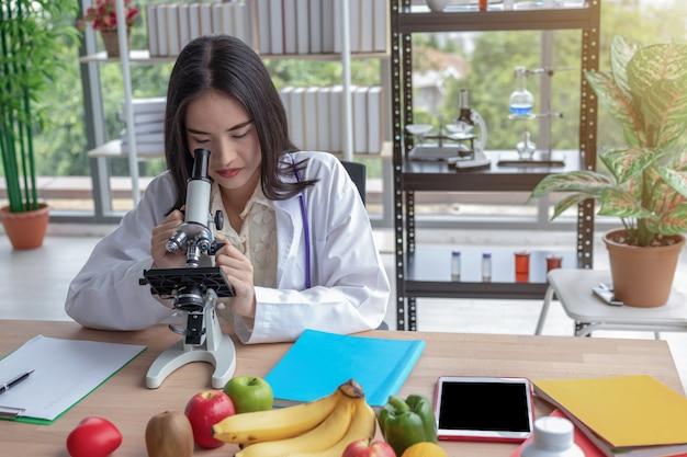 La femme médecin regarde au microscope.