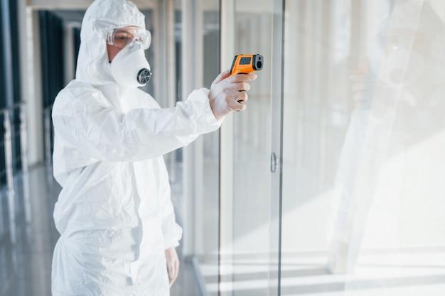 Femme médecin scientifique en blouse de laboratoire, lunettes défensives et masque debout à l'intérieur avec thermomètre infrarouge