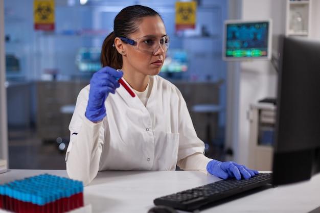 Femme médecin scientifique tenant un vacutainer médical avec une expertise en typage sanguin