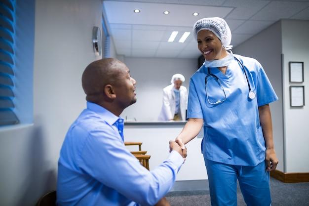 Femme médecin se serrant la main avec le patient