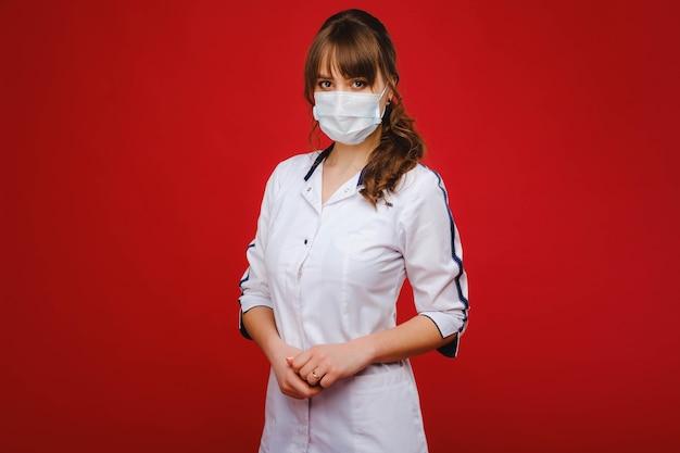 Une femme médecin se tient dans un masque médical isolé sur un fond rouge