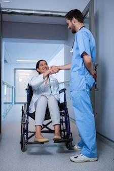 Femme médecin, séance, sur, fauteuil roulant, et, serrer main, à, mâle, infirmière