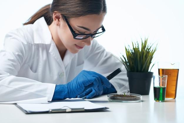 Femme médecin solutions chimiques biologiste recherche étude fond clair