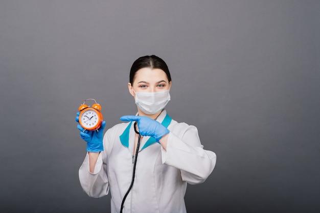 Femme médecin souriante en masque pointant sur l'horloge, l'heure de la vaccination, le concept médical