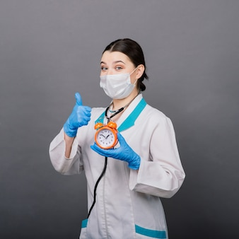 Femme médecin souriante en masque pointant sur l'horloge, l'heure de la vaccination