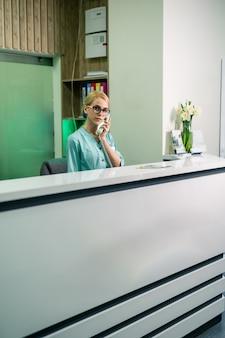 Femme médecin souriante tenant un récepteur et répondant aux appels téléphoniques, service médical. zone de réception.