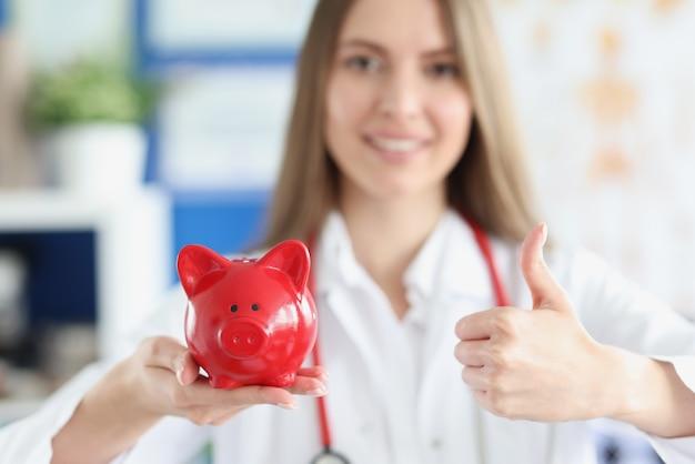 Femme médecin souriante tenant une tirelire cochon rouge et les pouces vers le haut