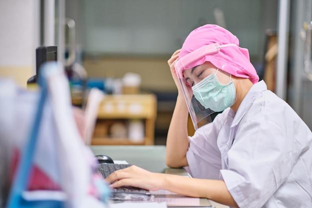 Femme médecin sous stress et maux de tête dormir devant l'ordinateur