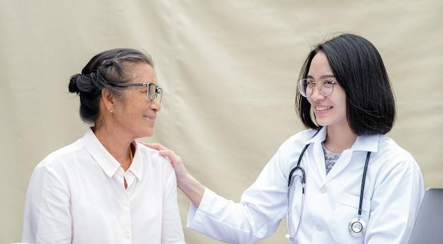 La femme médecin soutient les patients sur les épaules des personnes âgées et guide des soins de santé conviviaux