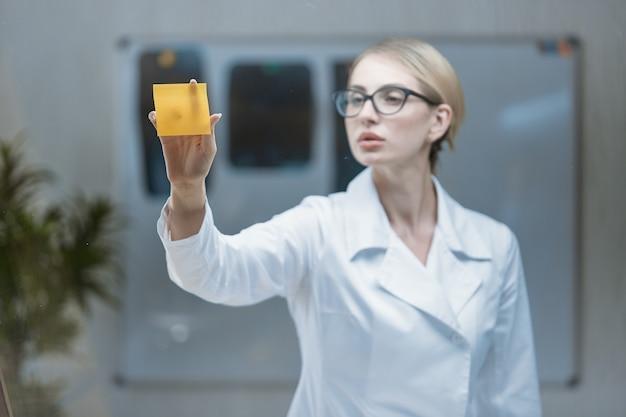 Une femme médecin avec un stéthoscope autour du cou colle des autocollants sur un verre transparent.
