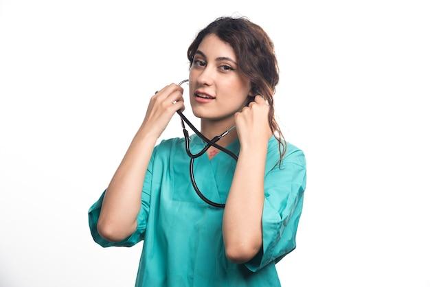 Femme médecin avec stéthoscope sur fond blanc
