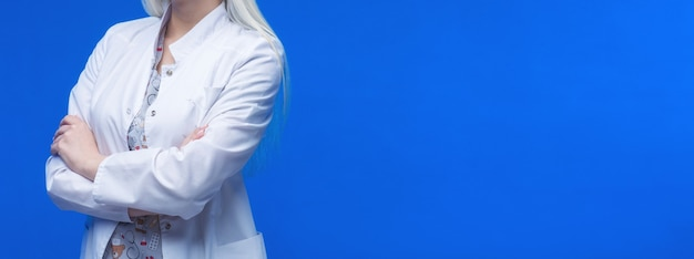 Femme médecin avec stéthoscope en fond bleu.