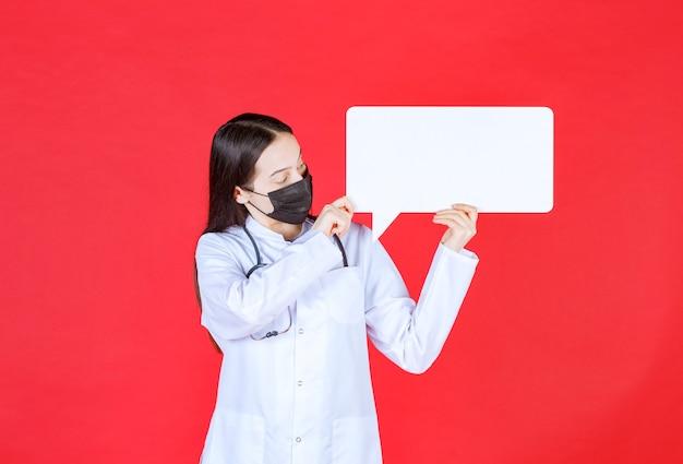Femme médecin avec stéthoscope et masque noir tenant un bureau d'informations rectangulaire.
