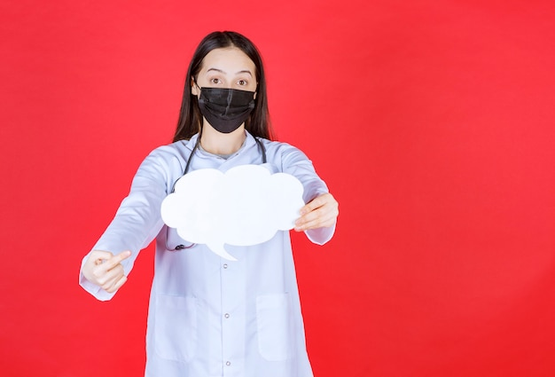 Femme médecin avec stéthoscope et masque noir tenant un bureau d'informations vide en forme de nuage.