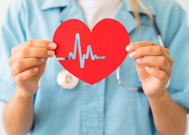 Femme médecin avec stéthoscope tenant coeur de papier avec rythme cardiaque