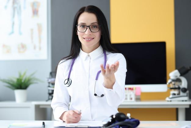 Femme médecin avec stréthoscope assis à table au bureau. concept d'assurance maladie