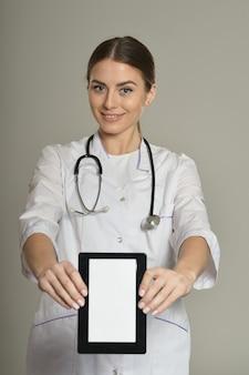 Femme médecin avec tablet pc, debout sur fond gris