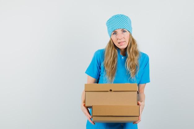 Femme médecin tenant des boîtes en carton en uniforme bleu