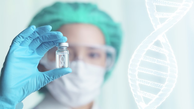 Femme médecin tenant une bouteille en verre transparent avec l'icône d'adn à l'intérieur de sa main.