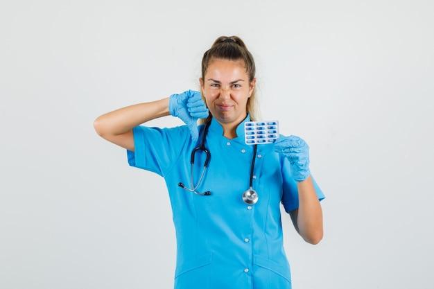 Femme médecin tenant des capsules avec le pouce vers le bas en uniforme bleu