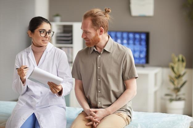 Femme médecin tenant une carte médicale et racontant les méthodes de traitement au patient lors de sa visite