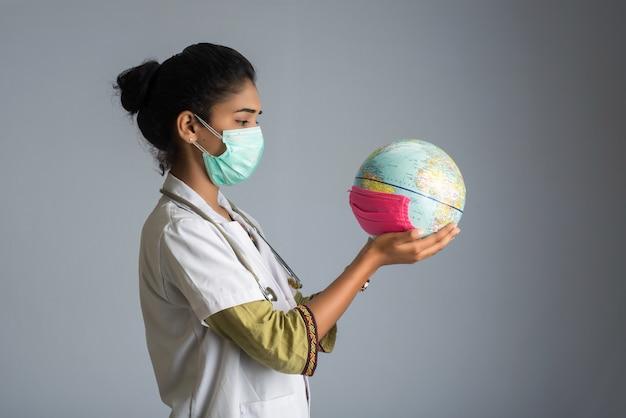 Femme médecin tenant un globe terrestre avec un masque de médecine. épidémie mondiale de concept de coronavirus.